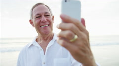 Caucasian senior male video call with family on the beach Stock Footage