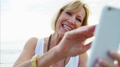 Attractive Caucasian senior female video call with family on the beach Stock Footage