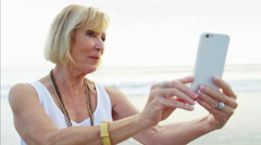 Fit Caucasian senior woman online chat with grandchildren on the beach Stock Footage