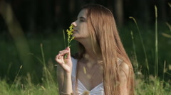 Genuine woman in meadow sniffing flower. Stock Footage