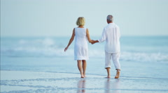 Loving retired Caucasian couple in white clothing relaxing on the beach Stock Footage