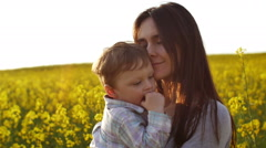 Mother holding her son at field at sunset. Slow mo Stock Footage