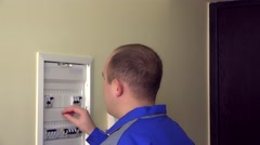 Man in blue uniform turn on circuit breakers on panel box at flat house Stock Footage