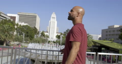 Mixed race man turns to camera in front of LA City Hall 4K Stock Footage