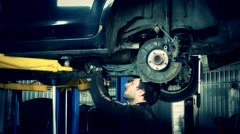 Mechanic renew brake system of a vehicle on a car lift. Zoom out Stock Footage