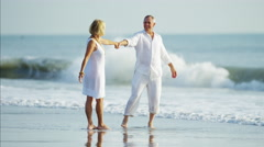 Healthy retired Caucasian couple having fun on their beach vacation Stock Footage