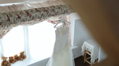 Wedding dress is hung up on cornice in bridal boudoir Stock Footage
