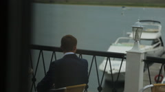 Man in black suit sits on berth awaiting for his companion - stock footage