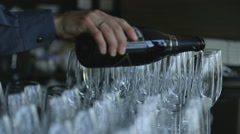 Groom pours sparkling champagne in narrow glass goblets standing on table Stock Footage