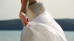 Fiancee in perfect bridal dress stands on berth near water - stock footage