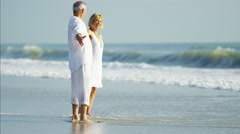 Carefree retired Caucasian couple dancing on their beach vacation Stock Footage