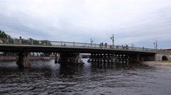 People walk on Ioanovskiy bridge in cloudy day, view from water Stock Footage
