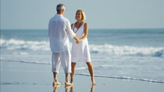 Loving mature Caucasian couple in white clothing relaxing on beach holiday Stock Footage
