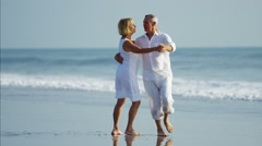 Healthy senior Caucasian couple in white clothing dancing on their beach holiday Stock Footage