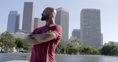 Mixed race man looks around with folded arms in Downtown LA 4K Stock Footage