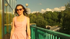 Slim brunette girl in pink dress walks on bridge. Slow motion steadicam clip - stock footage