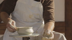 Artisan dressed in white apron sits outside workroom Stock Footage
