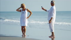 Senior Caucasian couple having fun with smartphone on beach vacation Stock Footage