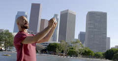 Mixed race man takes selfies in front of Downtown LA skyline 4K Stock Footage