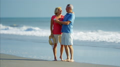 Senior Caucasian couple using smartphone technology on the beach Stock Footage