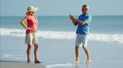 Senior Caucasian man taking a photo of senior woman wearing sunhat on the beach Stock Footage