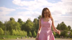 Thoughtful brunette girl in pink dress walks at camera. Slow motion steadicam Stock Footage