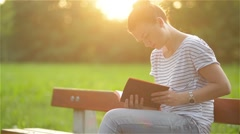 Beautiful Woman sitting on a bench in the park and reading a book, Student Stock Footage