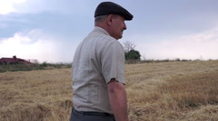 Old farmer walks through the field - stock footage