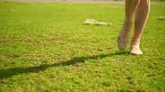 Slim brunette girl in pink dress walks at camera. Slow motion steadicam clip Stock Footage