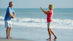 Senior Caucasian male posing to taking a picture on the beach Stock Footage
