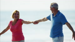 Carefree retired Caucasian couple having fun on their beach holiday Stock Footage