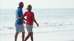 Loving senior Caucasian couple in colorful clothing relaxing on the ocean beach Stock Footage