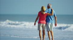 Loving Caucasian seniors in colourful clothing enjoying walking on the beach Stock Footage