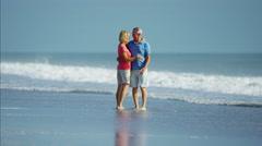 Healthy senior Caucasian couple enjoying walking beside the ocean Stock Footage