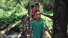 Hikers walking old bridge in rain forest jungle. Hiking family trekking throu Stock Footage