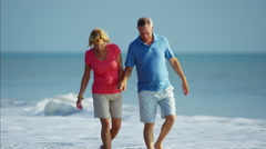 Loving retired Caucasian couple in colorful clothing relaxing on the beach Stock Footage