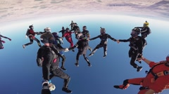 Professional skydivers make formation in blue sky. Sunny day. Open parachute Stock Footage