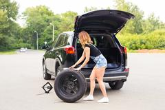 Woman changing tire on a road - stock photo
