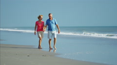 Retired Caucasian couple in colorful clothing relaxing on the ocean beach Stock Footage