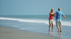 Healthy Caucasian seniors enjoying walking on the ocean beach Stock Footage