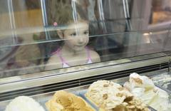 Little girl wishes ice cream in pastry shop - stock photo