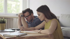 Angry young woman arguing with her husband about expenses and home finances Stock Footage