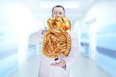 Doctor with stethoscope and golden digestive system on the hands in a hospita Stock Photos