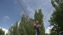 Boy jumping on a elastic band Stock Footage