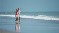 Senior Caucasian couple in colorful clothing enjoying walking beside the ocean Stock Footage