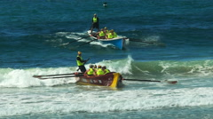 High angle close up of two surf boats catching waves at the end of a race Stock Footage