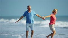 Healthy Caucasian seniors enjoying walking on their beach vacation Stock Footage