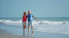 Carefree senior Caucasian couple having fun on their beach holiday Stock Footage