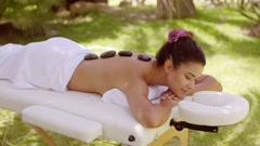Young woman enjoying a hot stone massage Stock Footage