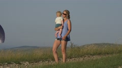 Mother with a baby walking in the background of paragliders Stock Footage